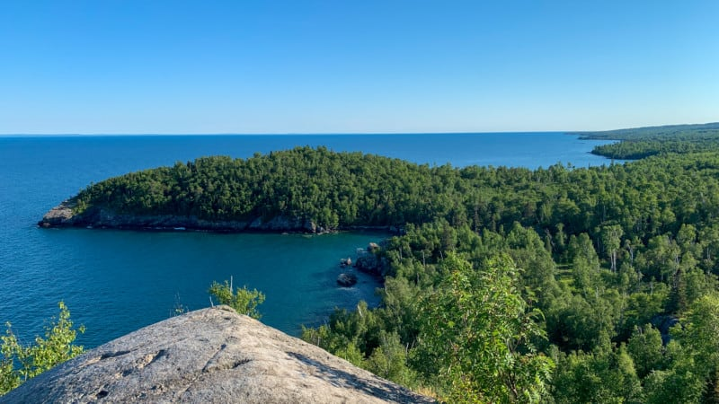 View from a large rock on a hill overlooking a wooded peninsula on Superior Lake in Split Lighthouse State Park, Minnesota