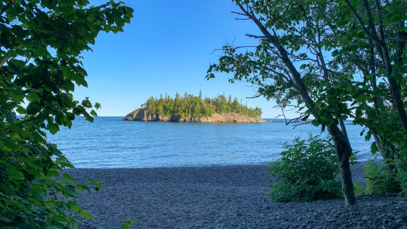 View of a wooded island on Lake Superior from a beach made of large, smooth pebbles.